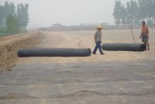 工人在现场铺设土工格栅