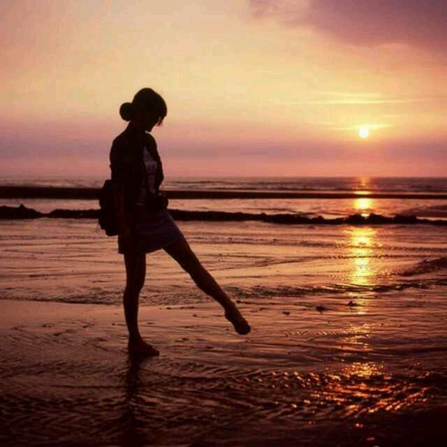 夕阳下的海边一个背着包的女生踢出左脚