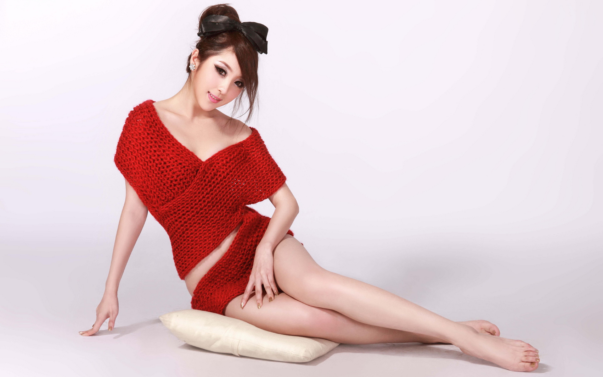 360壁纸中白色背景穿红色毛衣坐在地上露美腿的美女